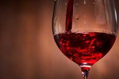 Närbild av smakligt rött vin som häller i det rena bräckliga vinglasanseendet mot träbakgrund Royaltyfri Bild