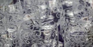 Närbild av snittet och cisiliated färglösa dricka exponeringsglas med abstrakta modeller royaltyfria foton