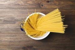 Närbild av spagetti inom en kruka på trätabellen Royaltyfria Bilder