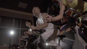 Närbild av sportgruppen av en man och två kvinnor som övar deras ben på stationära cyklar lager videofilmer
