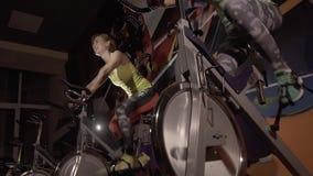 Närbild av sportiga unga kvinnor som använder den stationära cykeln för att utarbeta arkivfilmer