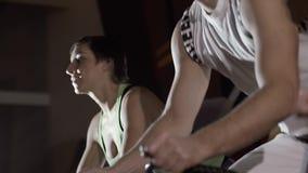 Närbild av sportigt folk i idrottshallen som övar på utbildningsapparaturen på natten arkivfilmer