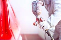 Närbild av sprutpistolen med röd målarfärg som målar en bil Royaltyfri Foto