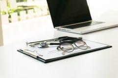 Närbild av stetoskopet, papper, bärbar dator på doktorstabellen Selectiv royaltyfria foton