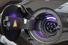 Närbild av strömförsörjningen som pluggas in i en elbil royaltyfri foto