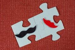 Närbild av 2 stycken av pusslet En symbolisk man med en mustasch och en kvinna med kanter Begreppet av psykologisk förenlighet Arkivfoton