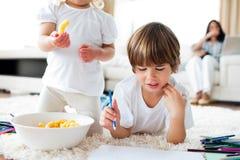 Närbild av syskon som äter chiper och att teckna Arkivfoto