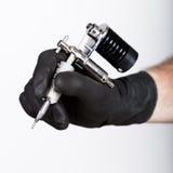 Närbild av Tattooisthänder i svarta handskar med tatueringmaskinen Fotografering för Bildbyråer