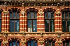 Närbild av tegelstenfasaden med fönster och kolonner i en gammal byggnad av Amsterdam Royaltyfri Bild