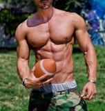 Närbild av torson av den mycket muskulösa mannen som är naken med fotboll Arkivbilder