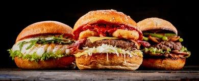 Närbild av tre olika hamburgare på tabellen Royaltyfri Bild