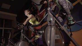Närbild av två aktiva konditionkvinnor som utbildar på motionscykeler i konditionstudio på natten arkivfilmer