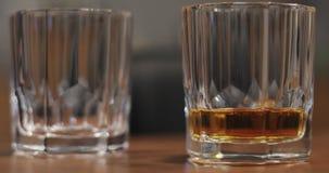 Närbild av två exponeringsglas av hälld whisky arkivfilmer