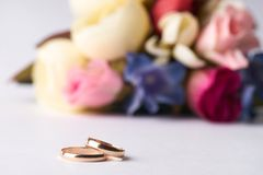 Närbild av två guld- vigselringar och bröllopbukett Fotografering för Bildbyråer