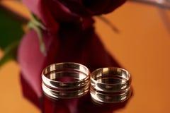 Närbild av två guld- vigselringar och bröllopbukett Arkivfoto
