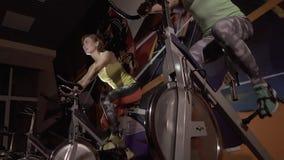 Närbild av två idrotts- unga kvinnor som använder stationära cyklar lager videofilmer