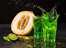 Närbild av två plaskande coctailar för ljus dragon på en svart bakgrund Grön dragon, klippt melon och sur limefrukt Royaltyfri Fotografi