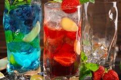 Närbild av två söta ljusa coctailar med mintkaramellen, limefrukt, is och bär som en bakgrund Uppfriskande sommardrycker för part Arkivbild