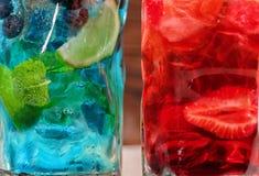 Närbild av två söta ljusa coctailar med mintkaramellen, limefrukt, is och jordgubbar som en bakgrund Uppfriskande sommardrycker f Royaltyfri Foto
