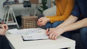 Närbild av undertecknande överenskommelse för man som tar tangent och skakar fastighetsmäklares hand på tabellen arkivfilmer