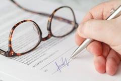 Närbild av underteckning av ett avtal Arkivfoto