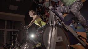 Närbild av unga sportiga kvinnor som vänder pedalerna av stationära cyklar stock video