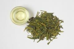 Närbild av varmt grönt te LongJing i kopp Dragon Well te Top beskådar Lekmanna- lägenhet Arkivbild