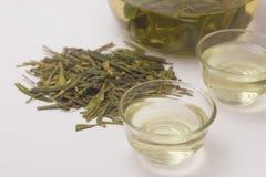 Närbild av varmt grönt te LongJing i koppar Dragon Well te Royaltyfri Bild