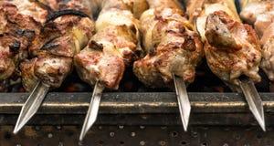 Närbild av varmt grillat kött på metallsteknålar royaltyfria bilder