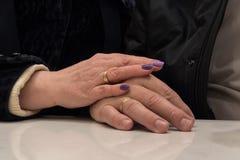 Närbild av vuxna gift parinnehavhänder royaltyfri bild