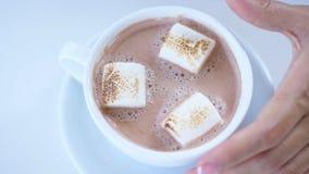 Närbild bästa sikt, vit kopp med cappuccino, med tjockt krämigt skum och marshmallower en hand för kvinna` s rör långsamt arkivfilmer
