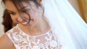 Närbild brudavgifter bruden kläs för bröllopet ståenden av ett härligt som ler bruden, skyler och snör åt in stock video