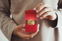 Närbild en man som öppnar den röda gåvaasken, med månen och stjärnorna inom, tappningsignal Royaltyfri Bild