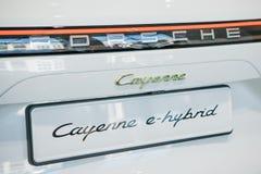 Närbild En ny bilPorsche Cayenne E-bland arkivfoto