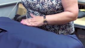 Närbild: En sömmerskakvinna ångar ett omslag genom att använda ett gammalmodigt järn En kvinnas hand rymmer järnet och slätar lager videofilmer