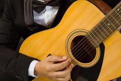 Närbild en ung man i en svart dräkt som spelar gitarren arkivfoto