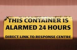 Närbild ett varningstecken som fästas till en låst sändningsbehållare som ses på en port royaltyfria foton