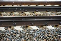 Närbild för järnvägspår och längsgående stödbjälke arkivfoto
