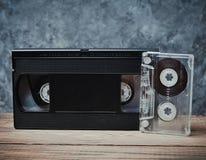Närbild för ljudsignal och videokassett på en trähylla mot en grå betongvägg Retro teknologi för att lyssna till musik royaltyfri foto
