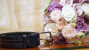Närbild härlig gifta sig bukett av rosmejeri, vitt och lila nära piskar män bältelögner Brud i den vita klänningen stock video