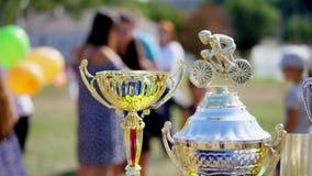 Närbild, härlig guld och silverkoppar, utmärkelser för utomhus- cykla konkurrens stock video