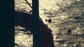 Närbild havsvågor på solnedgången, i strålarna av mjukt solljus Ilsken blick p? vattnet översikter av en livboj som hänger på arkivfilmer