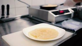 Närbild - kocken som lagar mat pannkakorna på en panna arkivfilmer