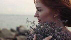 Närbild långsam rörelse Flicka med blommor på stranden med ett härligt utseende lager videofilmer
