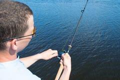 Närbild mot sjön, en man i gula exponeringsglas som rymmer en metspö för att fiska arkivfoto