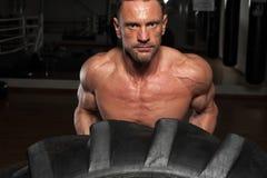 Närbild - muskulös stark man som lyfter det tunga däcket royaltyfri foto