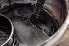 Närbild på behållaren med svart målarfärg för silver, medan blanda med spirala modeller i målningen royaltyfri foto
