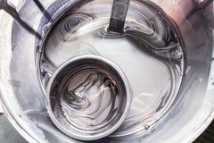 Närbild på behållaren med svart målarfärg för silver, medan blanda med spirala modeller i målningen och seminariet arkivbild