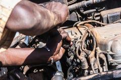 Närbild på en afrikansk man som arbetar på en bruten bilmotor royaltyfri bild