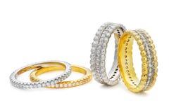 Närbild på fyra armband som göras av en guld och en silver med diam Arkivbilder